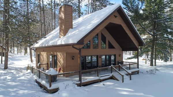 Snow covered wood cabin with surrounding deck