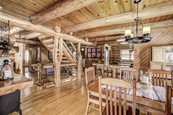 Wood paneling cabin interior with giant log beams