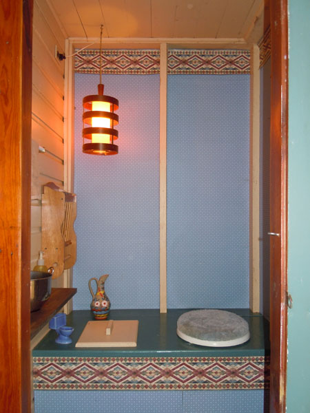 Interior of outhouse with toilet seat and lantern
