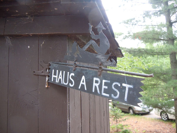 Haus a rest sign sticking out of the corner of a building