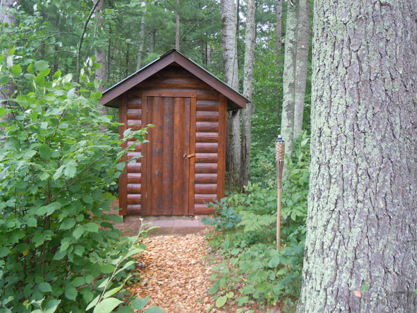 Outhouse built out of logs in the forest