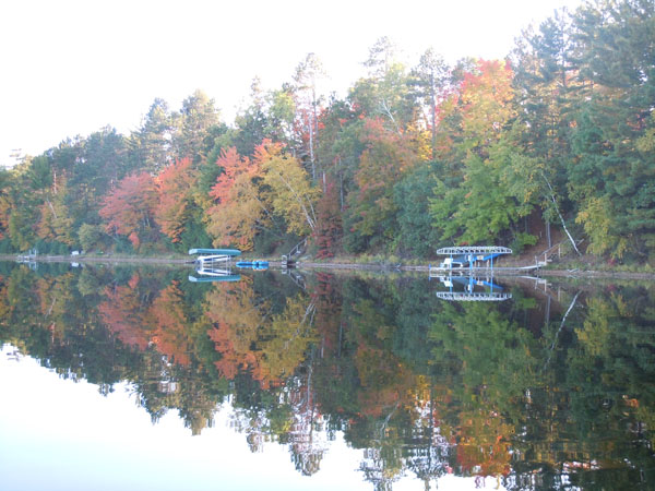 Fall foliage boats and docks reflecting onto lake