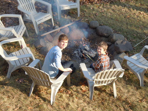 Two boys smiling and sitting by a large firepit