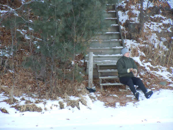 Man sitting by a lake on wood stairs in winter