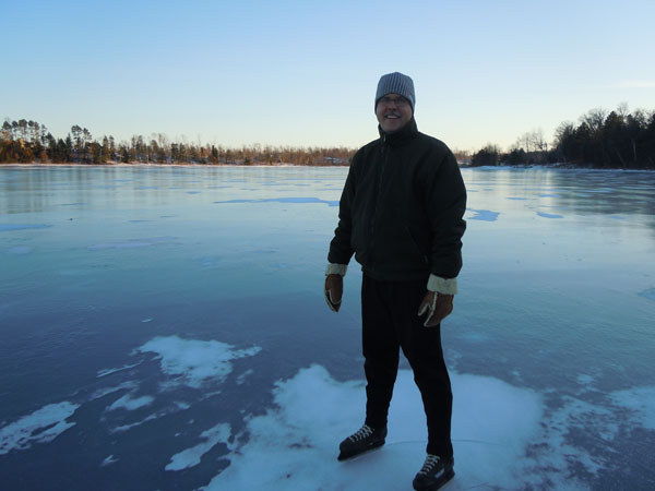 Man wearing ice skates and standing on frozen lake