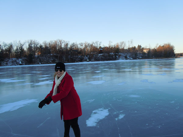 Woman in red coat smiling and skating on frozen lake