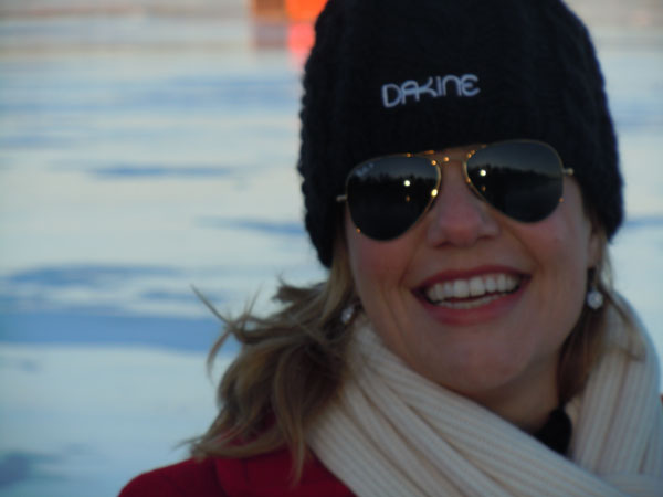 Close up of woman in sunglasses and hat smiling on frozen lake