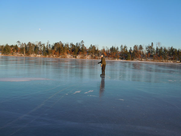Man skating on frozen lake in the distance