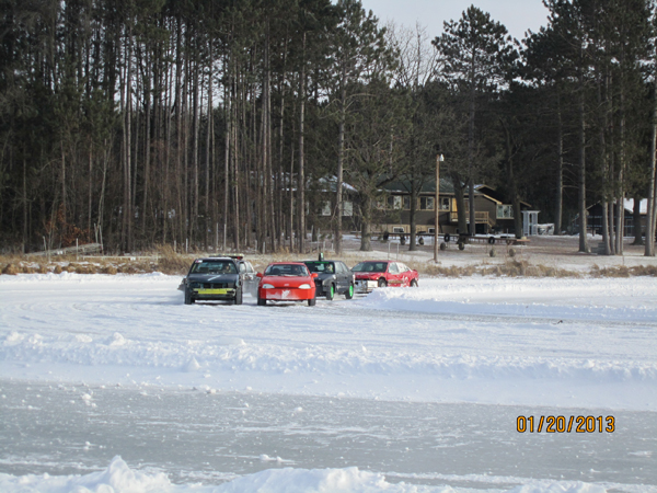 Cars going around snow shoveled track on frozen lake