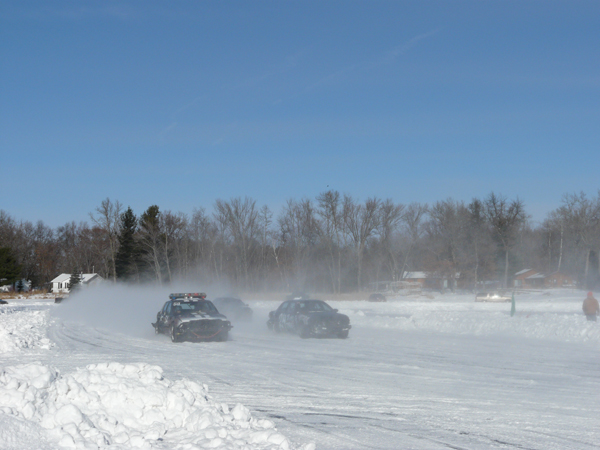 Racing cars kicking up snow on frozen Clam Lake