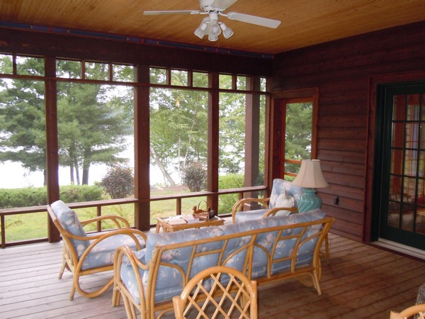 Screeen porch with wood floor and pale blue couches