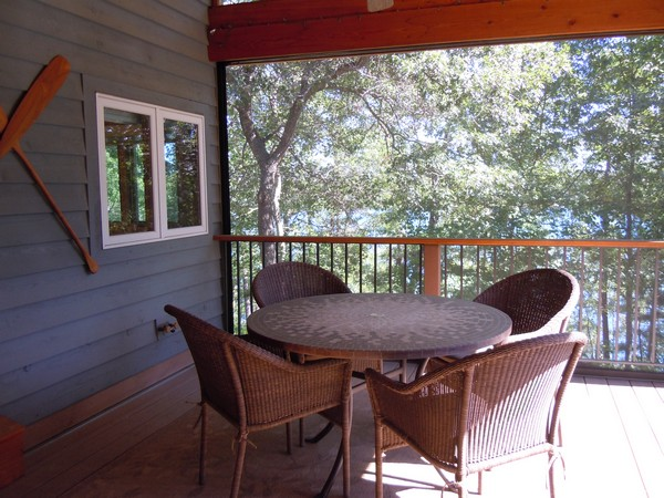 Screened in porch with dining area and railing