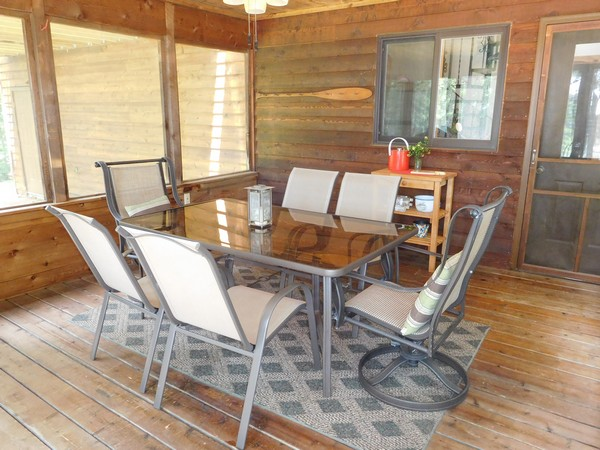 Screen porch with metal and glass dining table with porch chairs