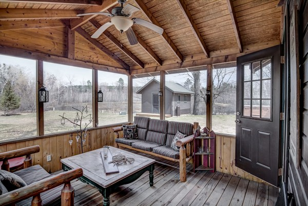 Screen porch with pale wood walls and seating area