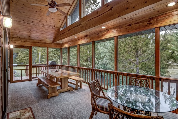 Screen porch with wood railing and wood dining table with benches