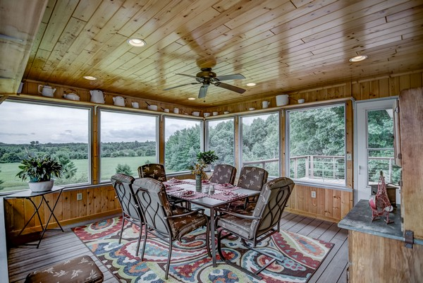 Screened in porch with ceiling fan and dining area with rug