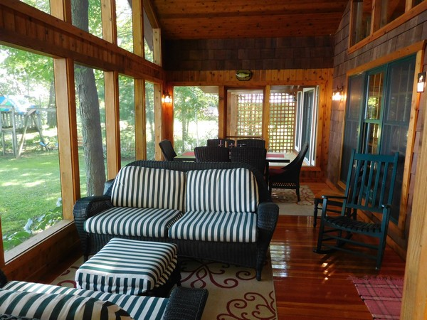 Screened in porch with tall windows and dining areas