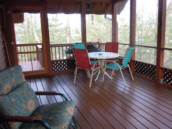 Screened in porch with small table and chairs and wood floors
