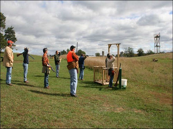 Men standing in a field with guns practicing shooting