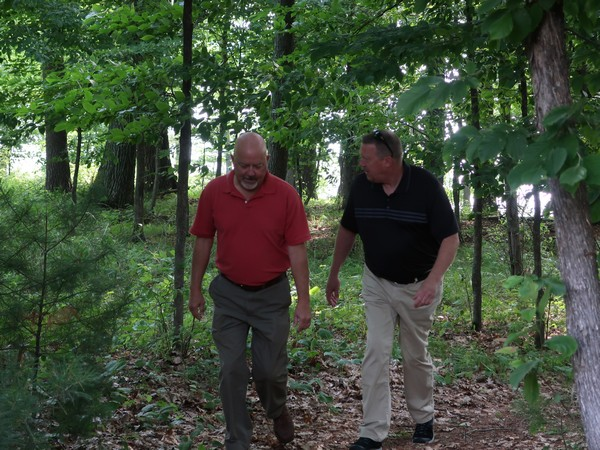 C21 agents walking through woods of lakefront property