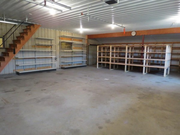 C21 Webster WI property with shelving units and cement floor