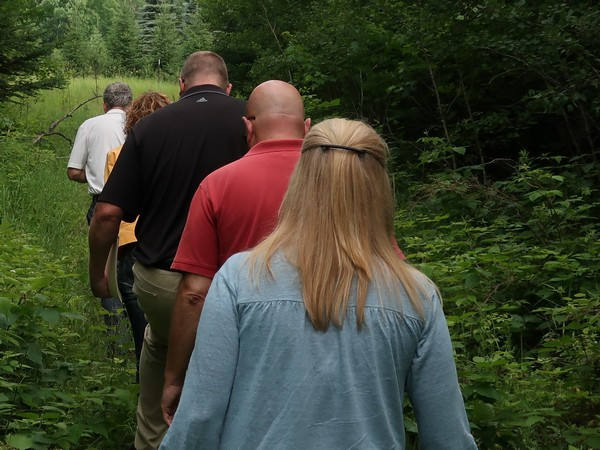 Century 21 agents walking through the forest of a property