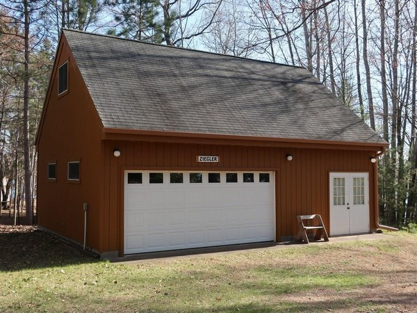 Brown garage with white doors and grey roof