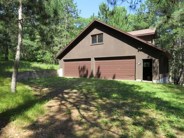 Century 21 Sand County light brown garage property