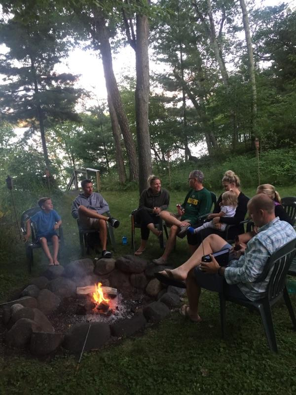 Family and friends gather around a campfire