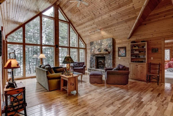 Great Room with wood burning fieldstone fireplace and a wall of glass toward the lake